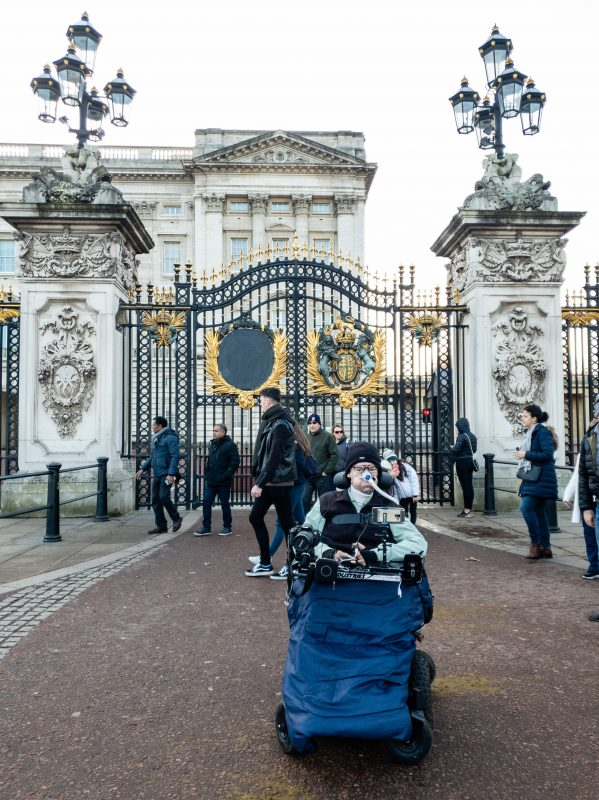 Daniel Baker sitting outside the gates of Buckingham Palace on his December London Trip