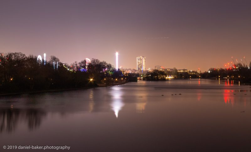 Winter Wonderland at night with London cityscape reflecting on the river in Hyde Park