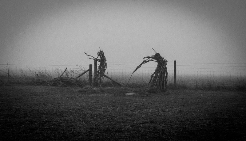 Black and white image on a misty day of the Rollright faeries, only two still stand