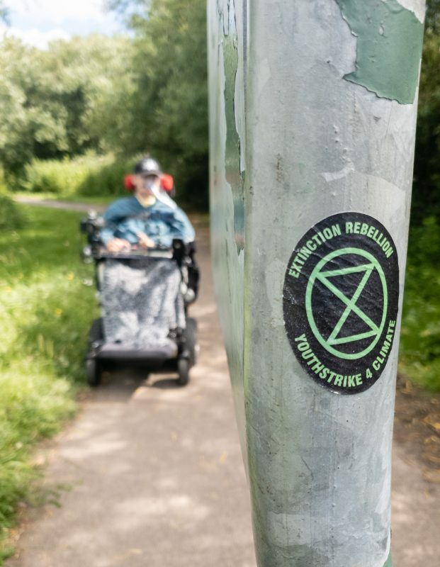 Daniel Baker on a path with a post in front of him showing an extinction rebellion sticker