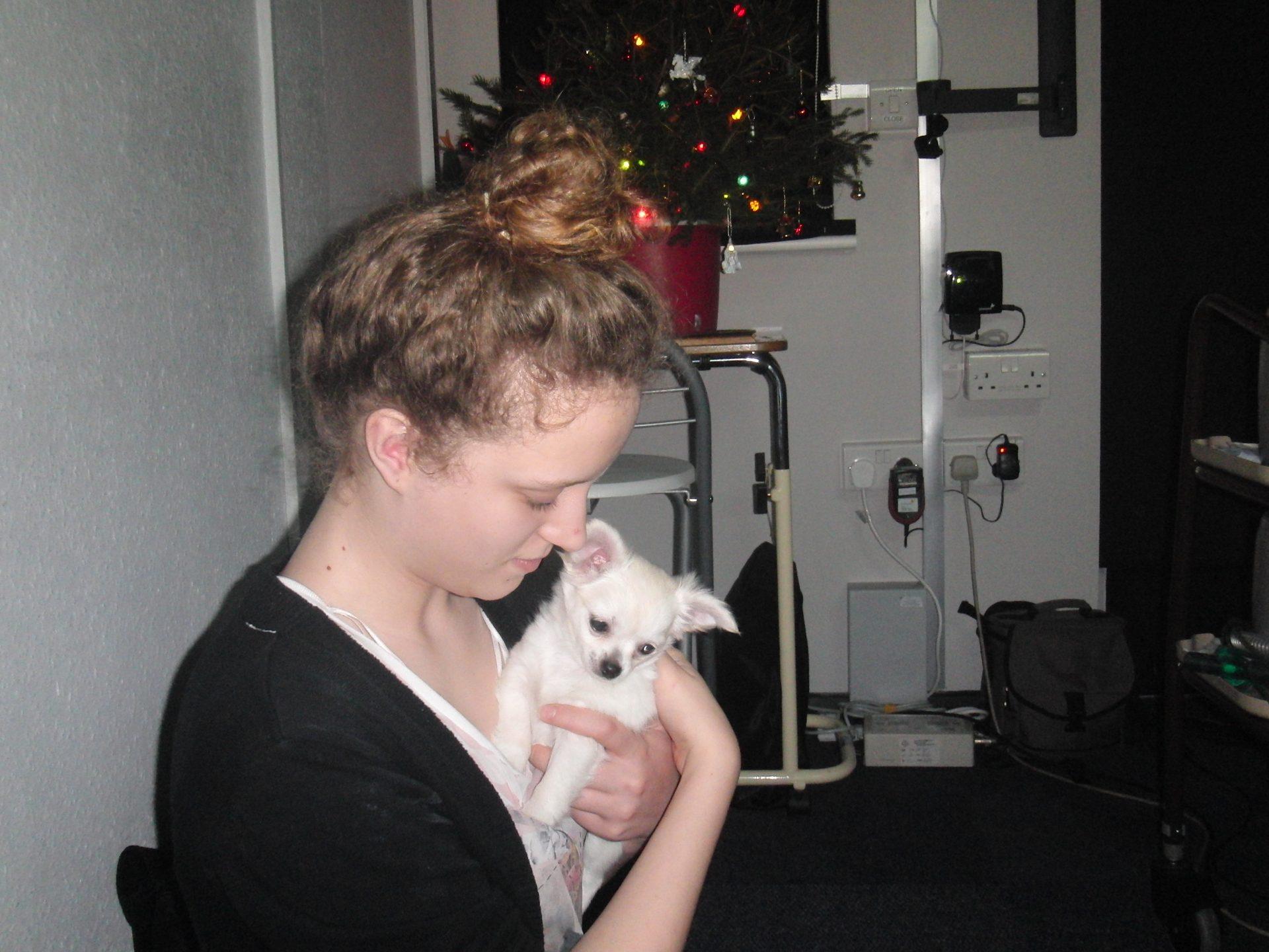 Daniel's Goddaughter holdin a white Chihuahua puppy