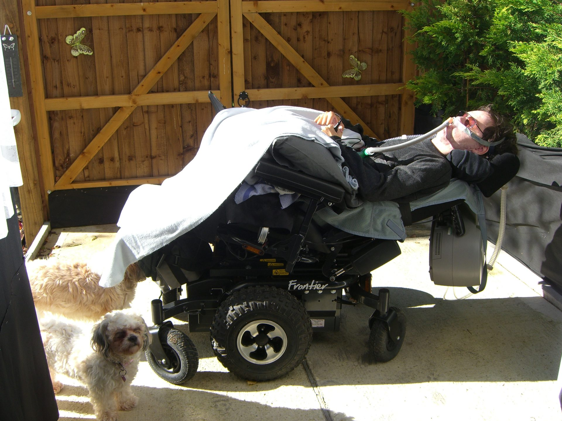 Daniel Baker reclined in his new wheelchair with a blanket draped over him