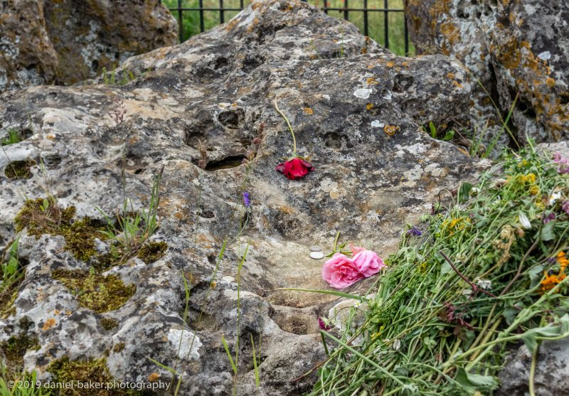 flowers and coins on an ancient stone at the Rollright stones