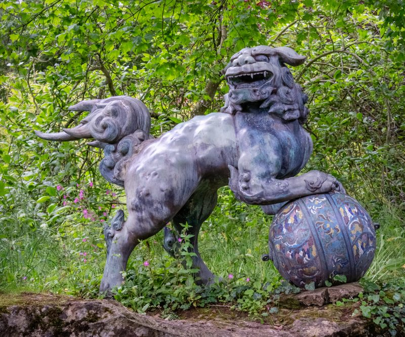 Chinese dragon sculpture with it's foot on a ball at Batsford Arboretum