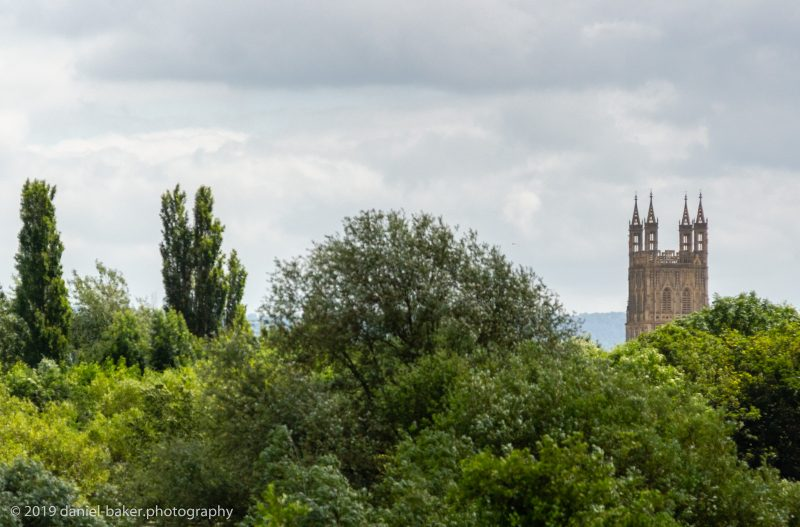 The top of Gloucester Cathedral with trees in front