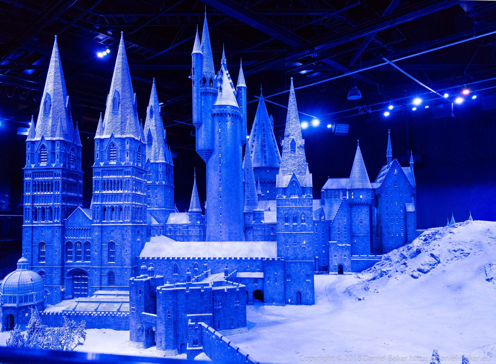 A model of Hogwarts in the snow lit by a blue light