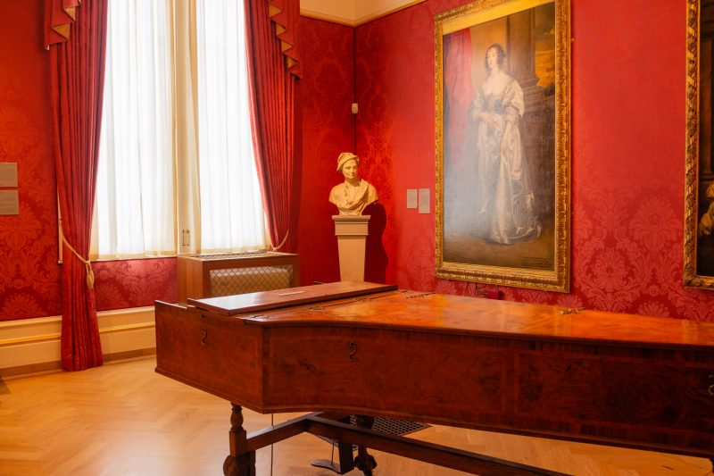 red wallpapered museum room with a piano, portraits on the wall and a bust in the corner at the Ashmolean Museum