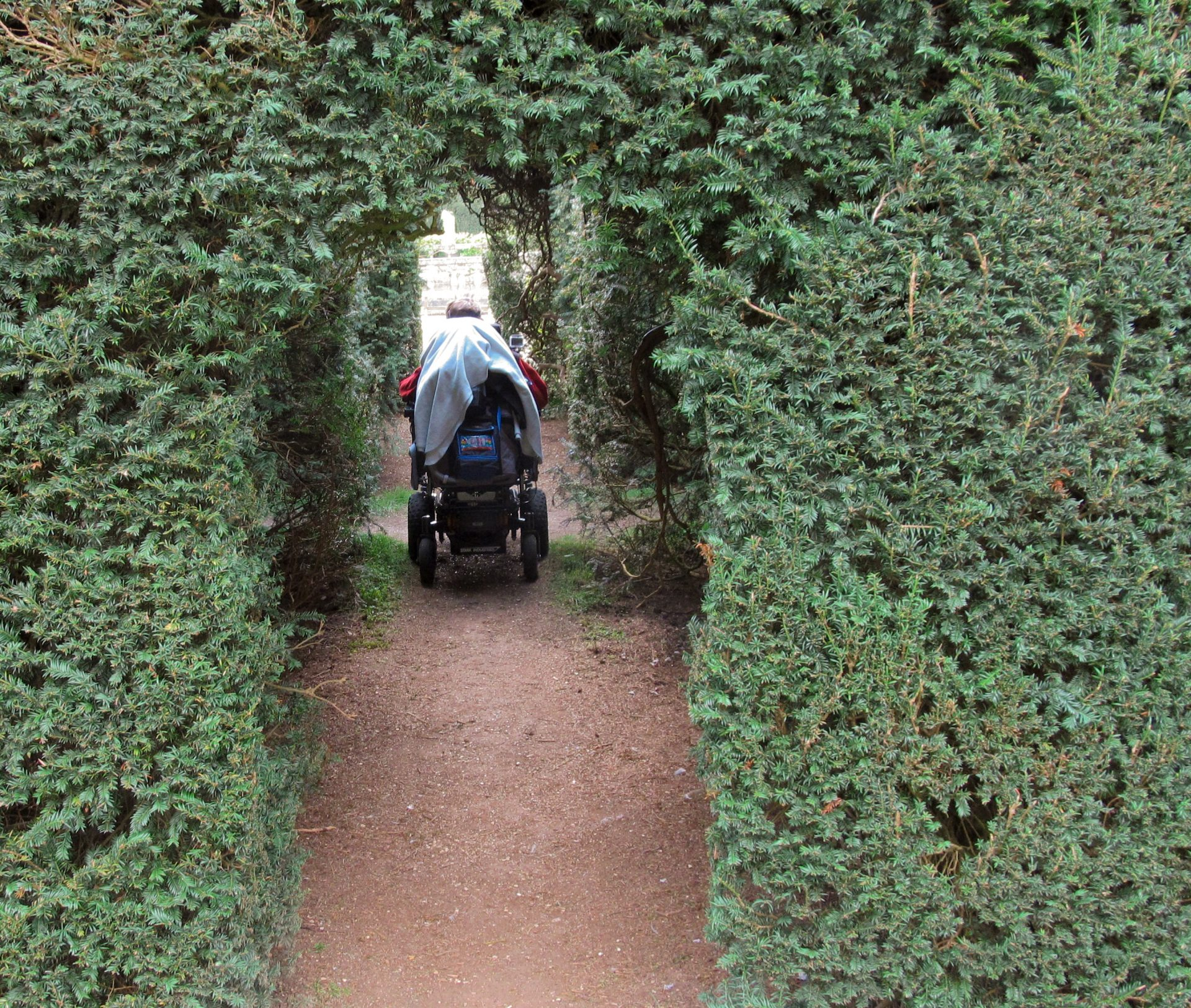 Daniel Baker in his wheelchair passing through archways cut in large hedges Looking Back to April 18th 2014 visit to Sudeley Castle