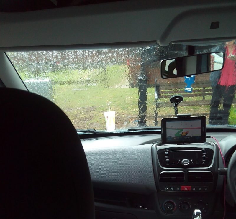 View from inside a van with rain on the windscreen and a woman barely visible dialling a number on her mobile phone