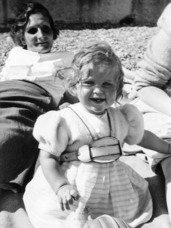 A black and white photo of a one year old girl on the beach