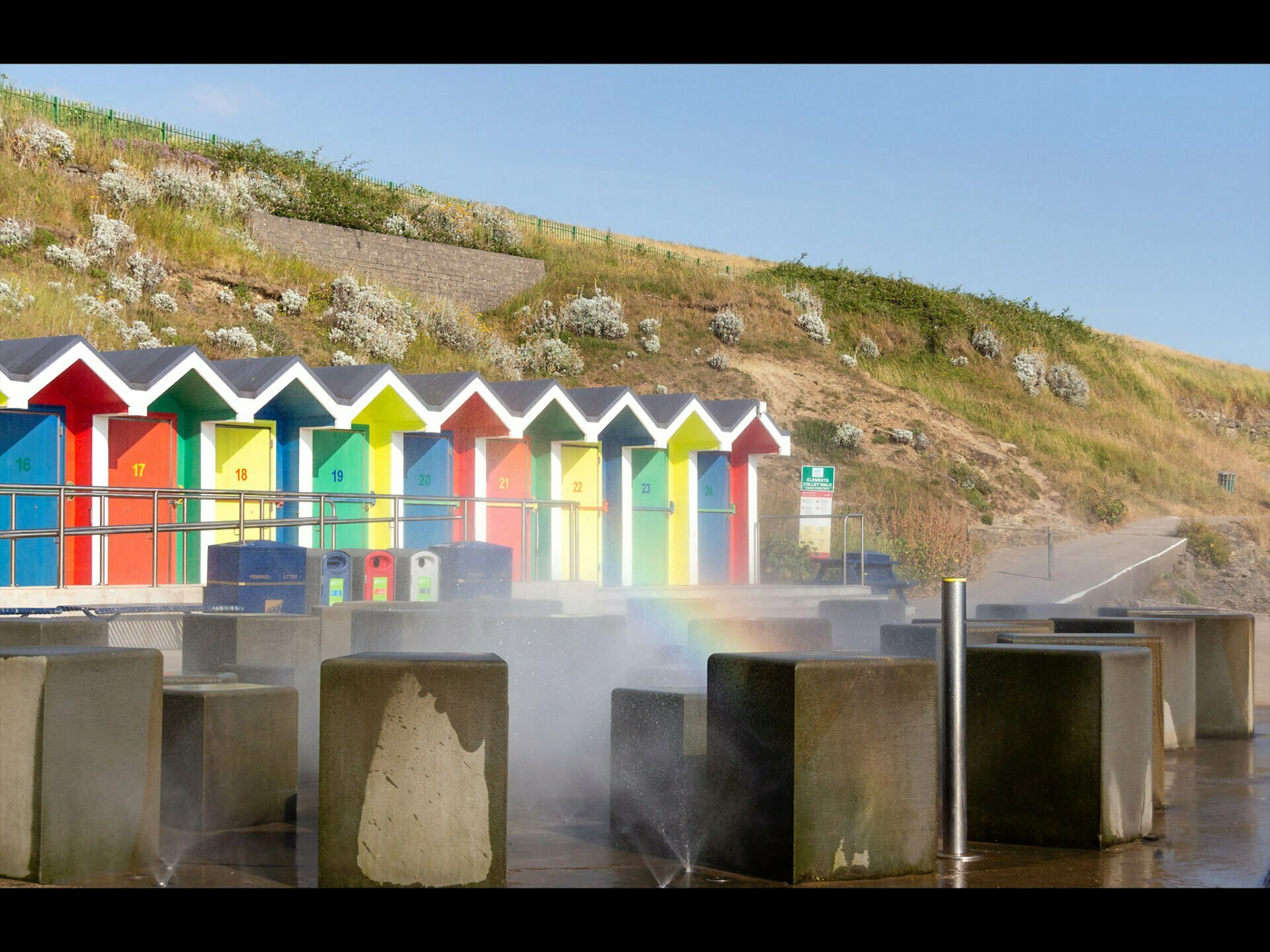 Colourful Beach hut with spray from a fountain causing a rainbow in front