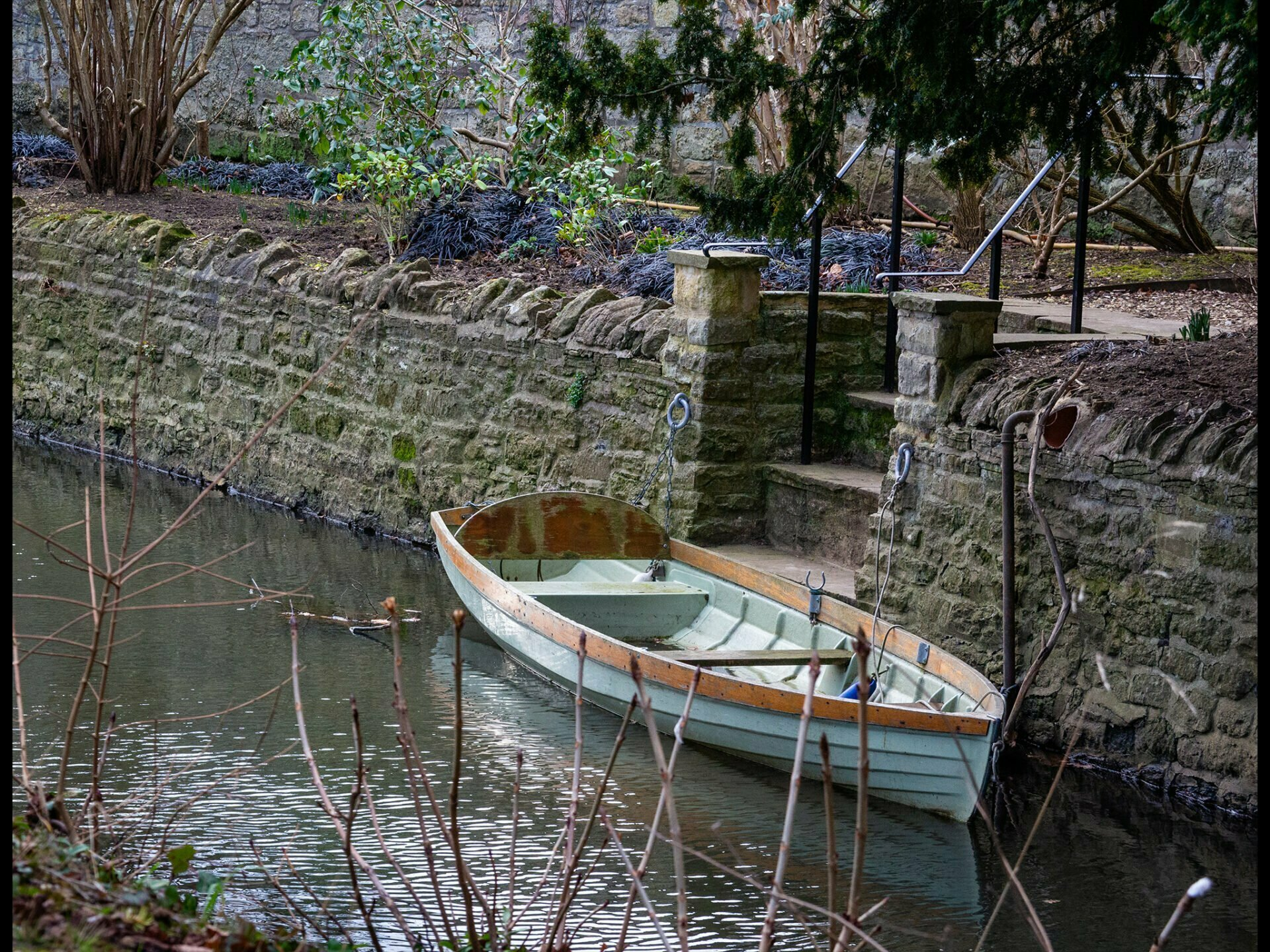 An old fashioned rowboat moored by some steps at Magdelen College