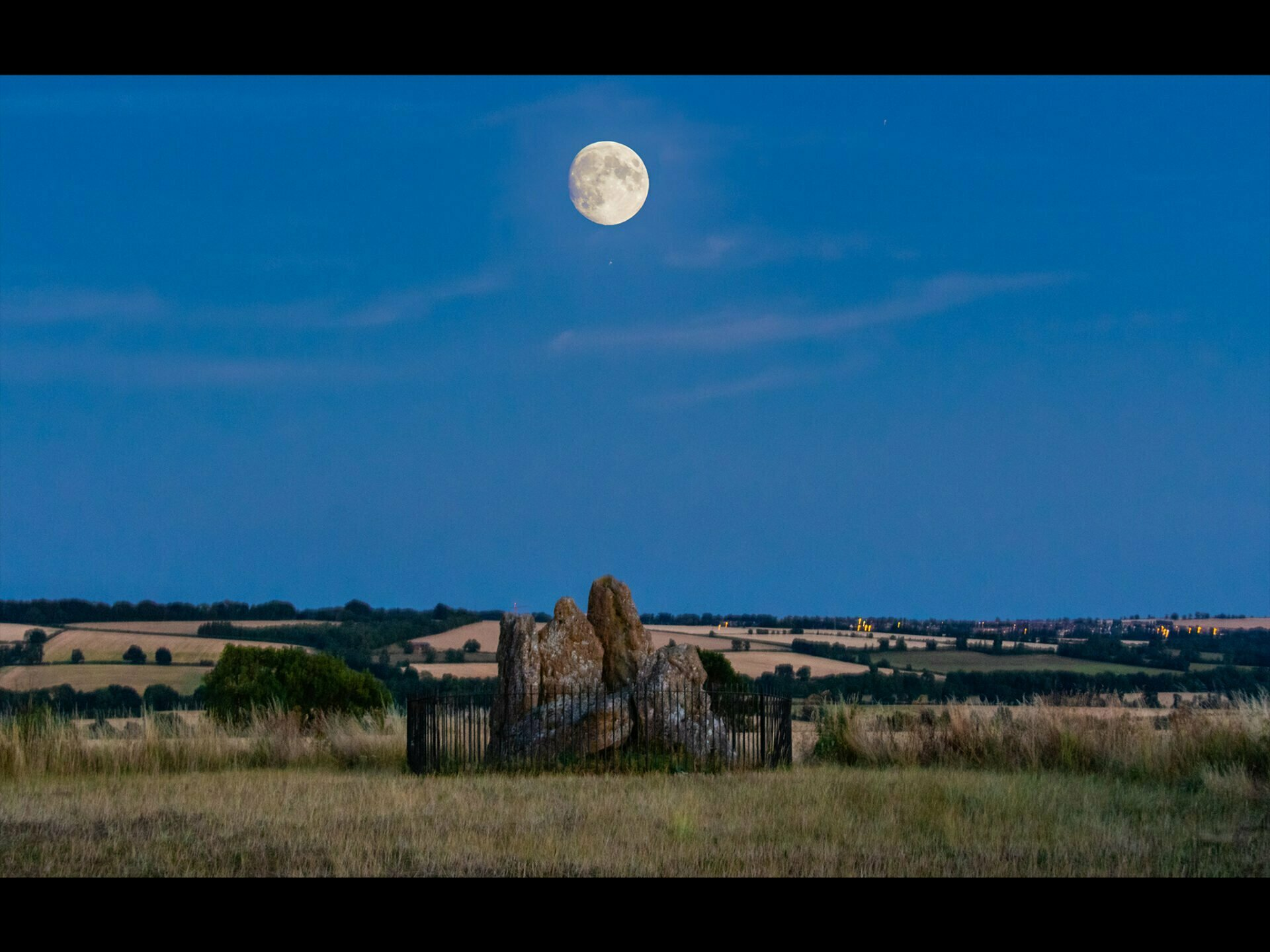 the moon above the whispering knights neolithic stones with a deep blue night sky
