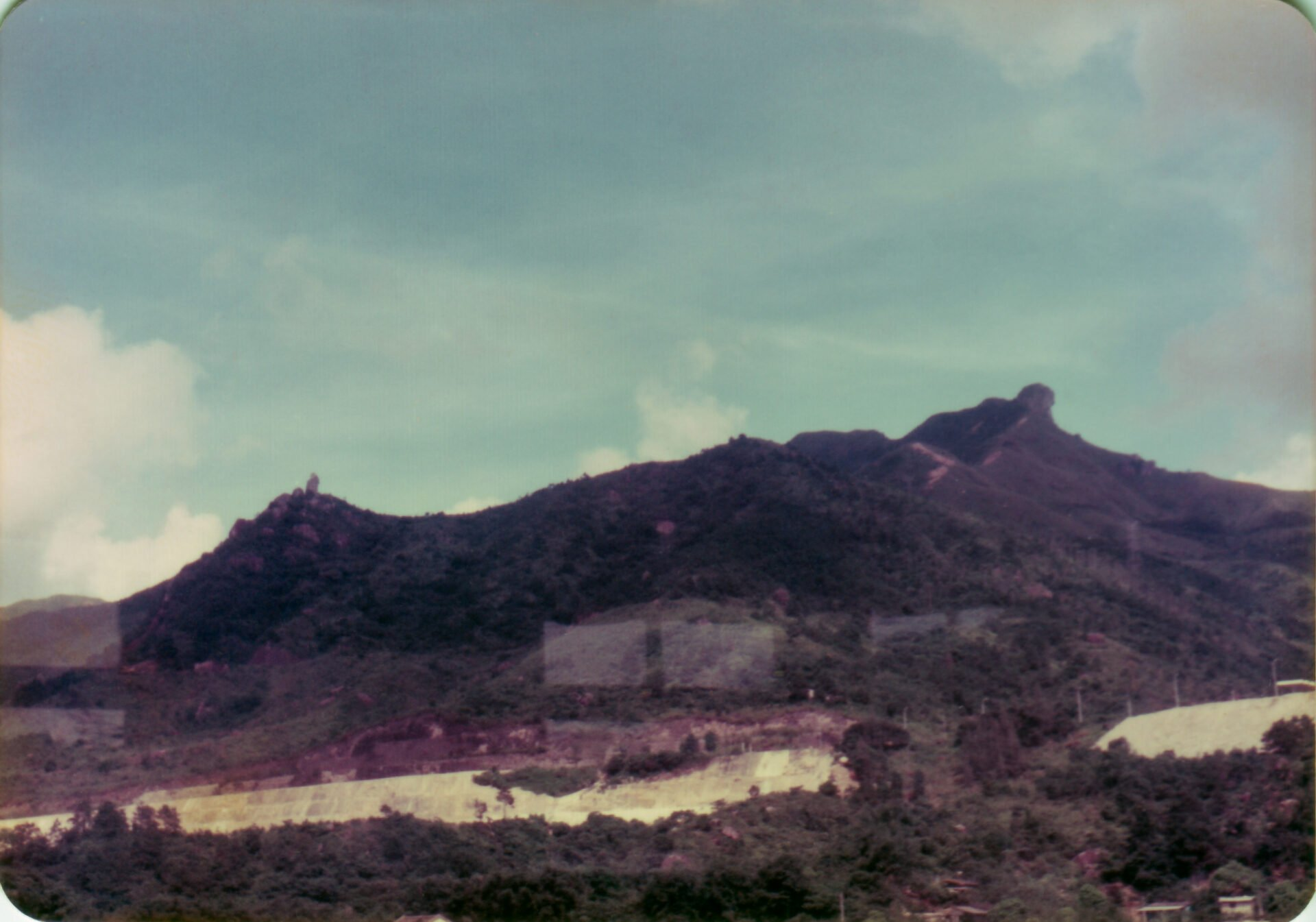 Hong Kong Lion rock right Amah rock left from train in new territories